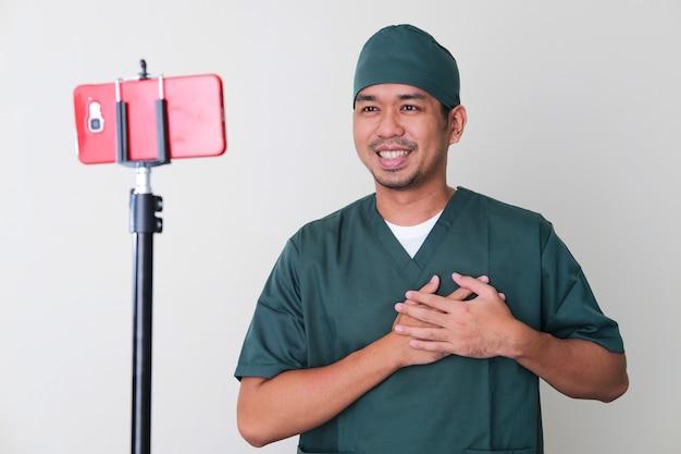Mannelijke ziekenhuisverpleegster die online overleg geeft met de patiënt met behulp van een videogesprek via een mobiele telefoon
