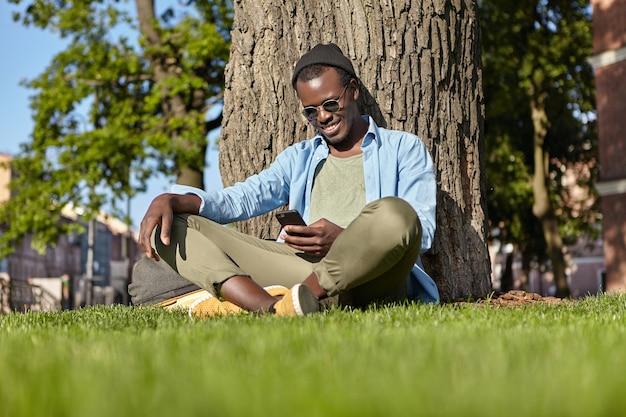 Mannelijke zittend op groen gras in de buurt van boom