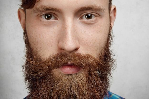 Mannelijkheid en macho. zeer gedetailleerde close-up shot van aantrekkelijke stijlvolle man met dikke pluizige baard en goed getrimde snor.