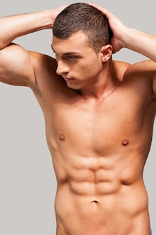 Mannelijkheid. knappe jonge shirtloze man die handen achter het hoofd houdt en wegkijkt terwijl hij tegen een grijze achtergrond staat