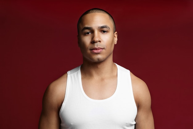 Mannelijkheid. kracht en machtsconcept. foto van knappe fit jonge afro-amerikaanse bodybuilder met kaal hoofd en glad geschoren gezicht camera kijken met zelfverzekerde ernstige gezichtsuitdrukking
