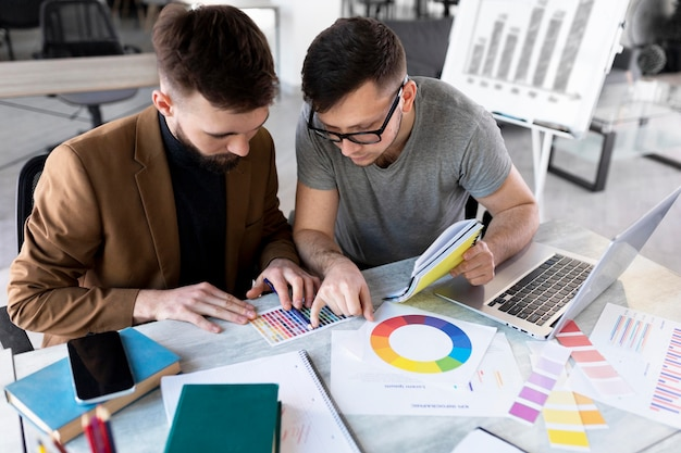Mannen analyseren een grafiek samen op het werk