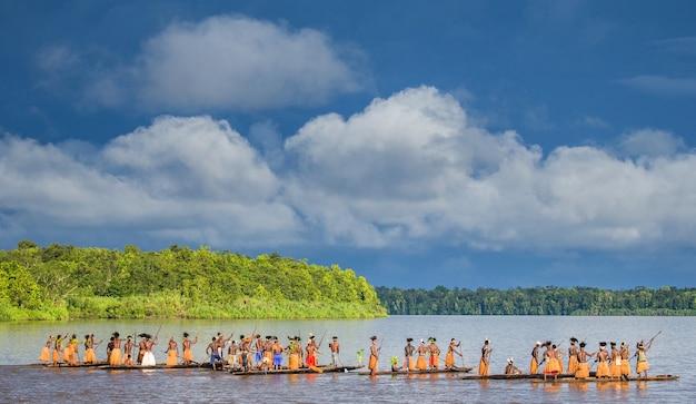 Mannen asmat-stam drijven in een kano op de rivier. amanamkay. dorp, provincie asmat, indonesië