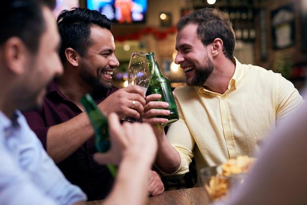 Mannen chillen met een drankje in de kroeg