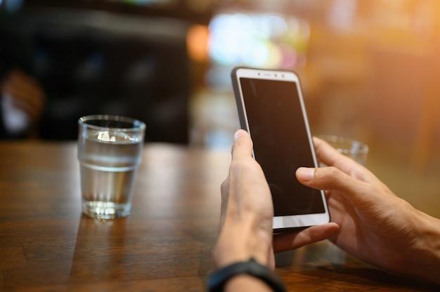 Mannen controleren e-mails met mobiele telefoons.