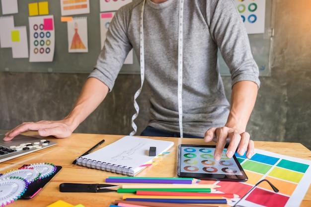 Mannen die als modeontwerper kiezen op kleurkaart voor kleding in digitale tablet op werkplaatsstudio.