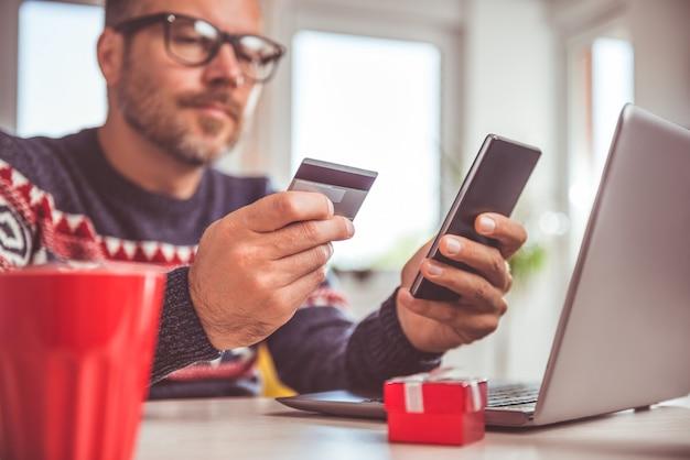 Mannen die creditcard houden en slimme telefoon thuis kantoor met behulp van
