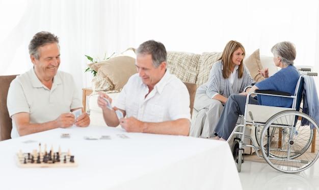 Mannen die kaarten spelen terwijl hun vrouw praat