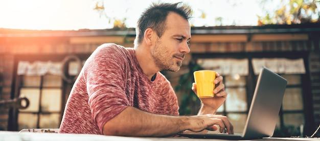 Mannen die koffie drinken en laptop met behulp van bij binnenpatio