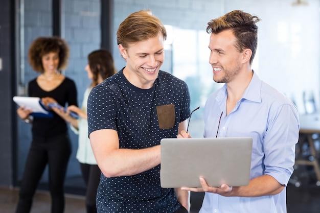 Mannen die laptop bekijken en een bespreking hebben terwijl collega's die zich in bureau erachter bevinden