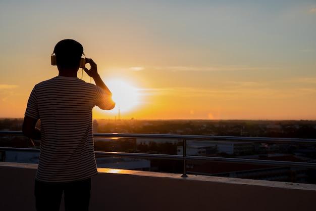 Mannen die op koptelefoon bij zonsondergang