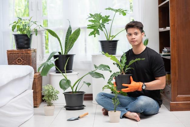 Mannen die oranje handschoenen dragen en bomen binnenshuis planten.