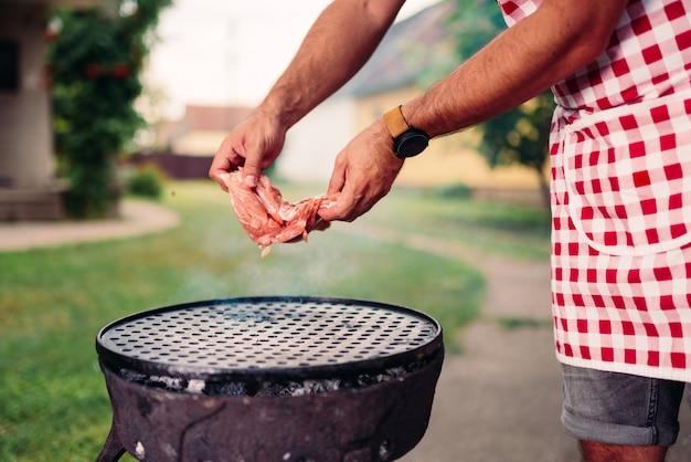 Mannen die schort dragen die kippenvlees voorbereidingen treffen te grillen