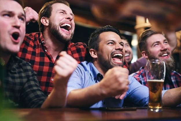 Mannen die televisie kijken en juichen voor team