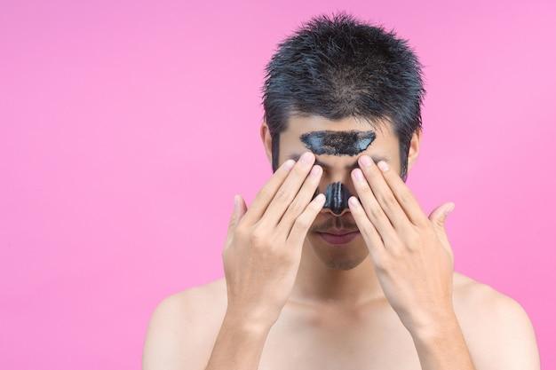 Mannen die twee handen gebruiken om hun gezicht te verbergen en zwarte cosmetica op hun gezicht hebben op een roze.