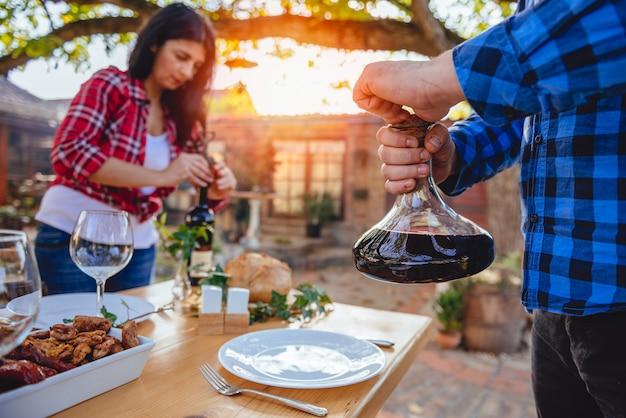 Mannen die wijnkaraf boven eettafel houden