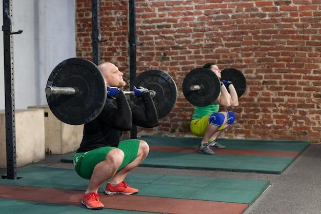 Mannen doen squat met halters
