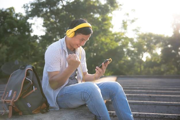 Mannen dragen een koptelefoon om mobiele telefoons te gebruiken om films te bekijken via de applicatie.