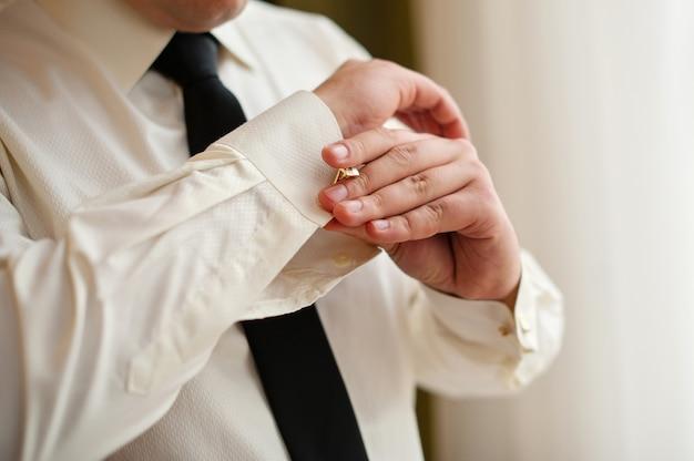 Mannen dragen manchetknopen op een mouw van een shirt