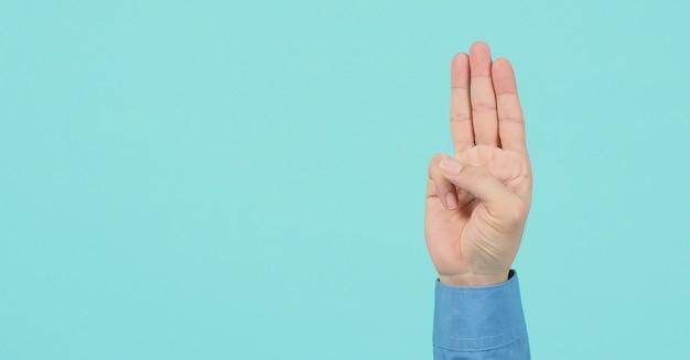 Mannen dragen shirt met lange mouwen doet een handteken van 3 vingers die naar boven wijzen, wat betekent dat drie, derde of gebruik in protest. het zet op blauwe of groene mint achtergrondgeluid