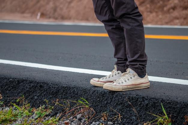 Mannen dragen sneakers op straat lopen met gele lijnen.