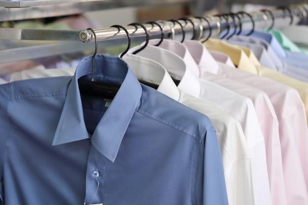 Mannen effen shirts op hangers in een winkel