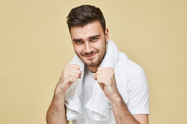 Mannen en mannelijkheid. portret van zelfverzekerde jonge brunette ongeschoren man met handdoek om de nek staande in de badkamer met gebalde vuisten voor hem, zijn eigen spiegelbeeld in de spiegel uitdagen