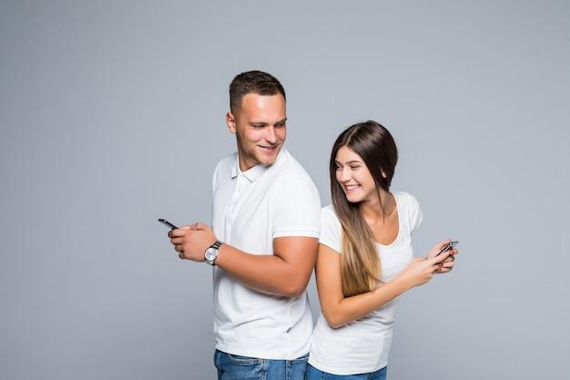 Mannen en vrouw lachend paar staande met mobiele telefoons in hun handen geïsoleerd op een grijze achtergrond