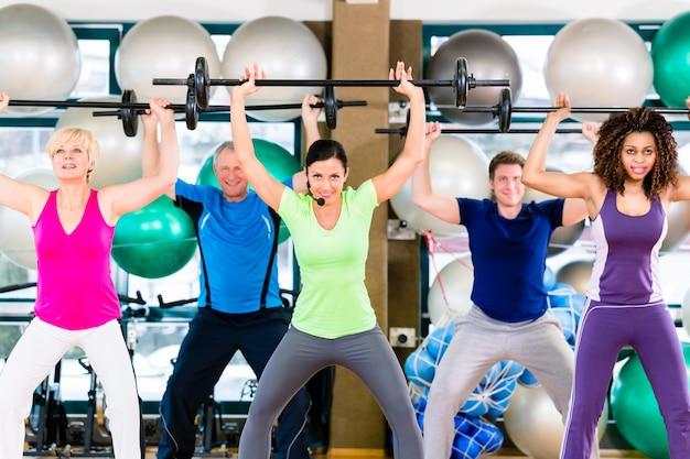 Mannen en vrouwen die halter in gymnastiek opheffen
