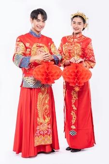 Mannen en vrouwen die qipao dragen die zich met honingraatlamp bevinden, die op witte achtergrond wordt geïsoleerd.