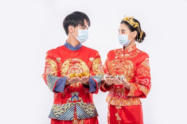 Mannen en vrouwen die qipao dragen en maskers dragen besteden met goudgeld