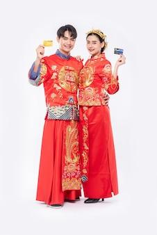 Mannen en vrouwen die qipao dragen, gaan winkelen met een creditcard.