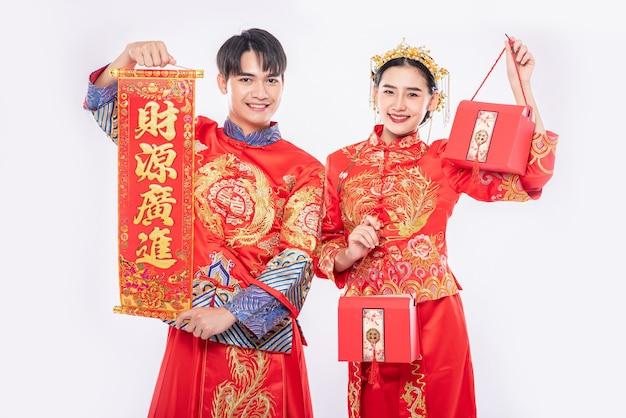 Mannen en vrouwen die staande cheongsam dragen, begroetingsborden vasthouden en rode tassen dragen