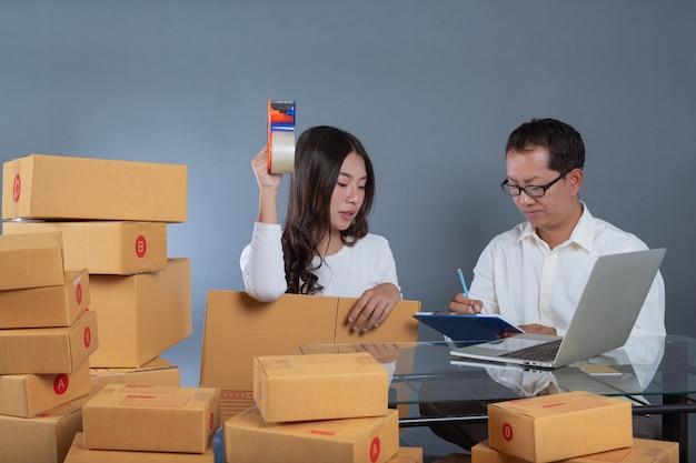 Mannen en vrouwen helpen de dozen in te pakken.