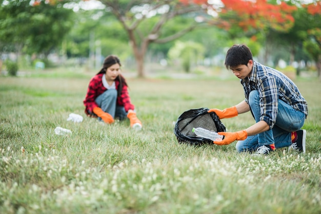 Mannen en vrouwen helpen elkaar bij het ophalen van afval.