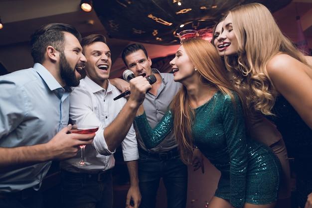 Mannen en vrouwen in de club zingen samen.