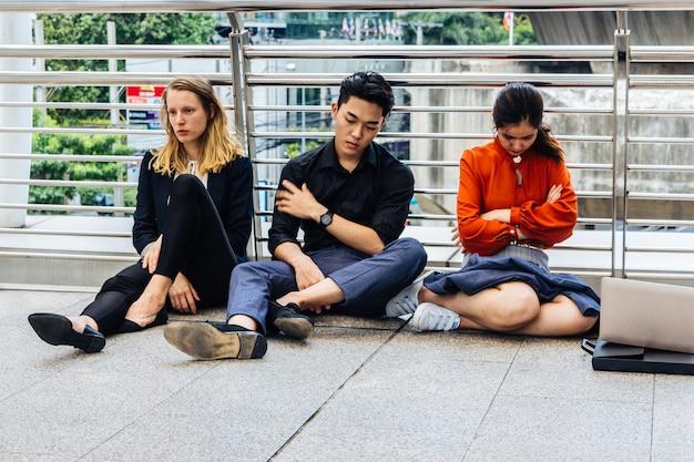 Mannen en vrouwen in werkkleding zitten op straat met sombere en wanhopige gezichten in het concept van een slechte economie en werkloosheid.