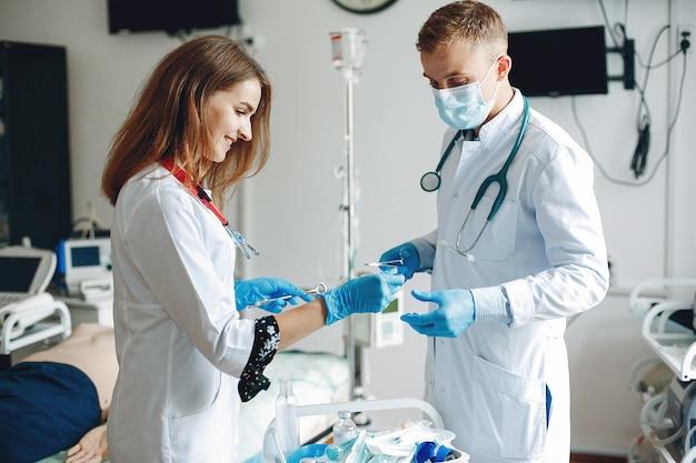 Mannen en vrouwen in ziekenhuisjassen hebben medische apparatuur in hun handen. de verpleegster draait het medicijn in de injectie.