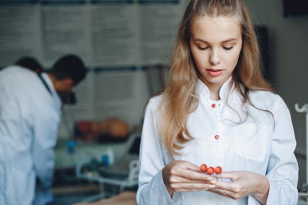 Mannen en vrouwen in ziekenhuisjassen studeren. verpleegster met reageerbuizen.