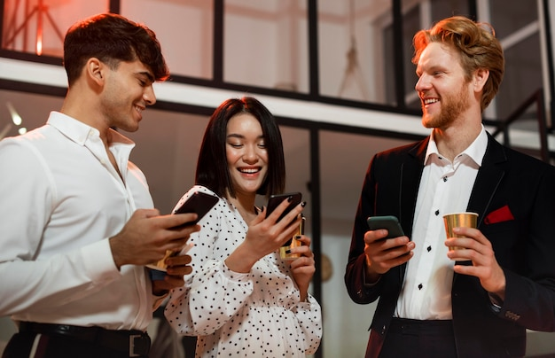 Mannen en vrouwen kijken op hun telefoon op oudejaarsavondfeest