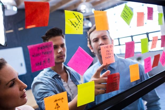 Mannen en vrouwen lezen een post-it op een raam