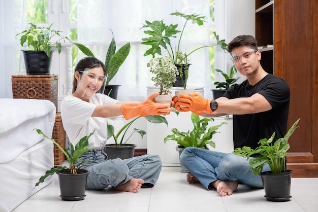 Mannen en vrouwen met oranje handschoenen zaten en plantten bomen in een huis.