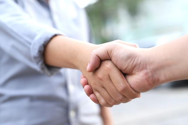 Mannen en vrouwen schudden elkaar de hand om elkaar te begroeten als ze elkaar van aangezicht tot aangezicht ontmoeten.