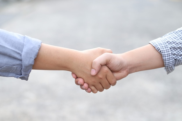 Mannen en vrouwen schudden elkaar de hand om elkaar te begroeten
