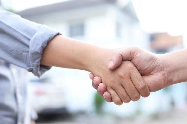 Mannen en vrouwen schudden elkaar de hand om in te stemmen met het kopen en verkopen van huizen.
