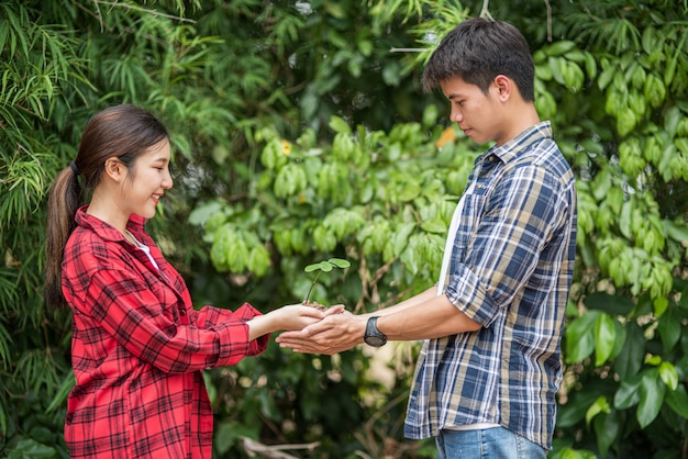 Mannen en vrouwen staan en houden jonge boompjes.