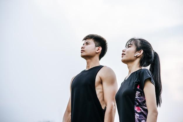 Mannen en vrouwen staan na het sporten naar de lucht te kijken.