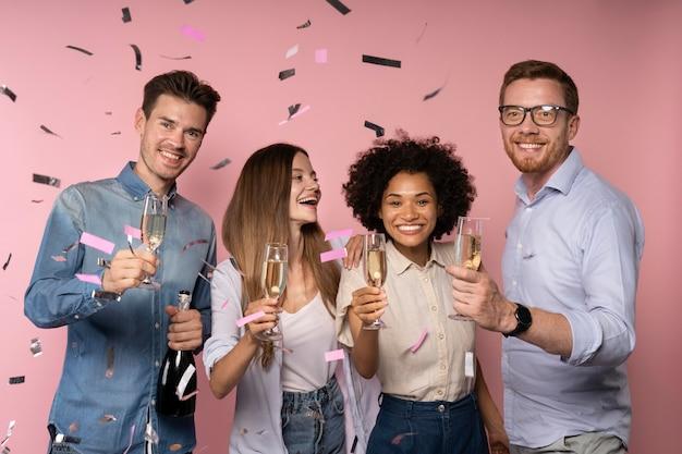 Mannen en vrouwen vieren met champagneglazen en confetti
