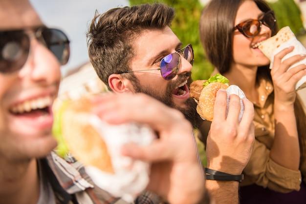 Mannen en vrouwen zitten buiten en eten.