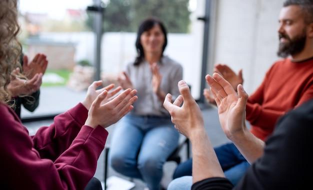 Mannen en vrouwen zitten in een kring tijdens groepstherapie, klappend.